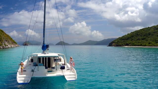 vídeos de stock e filmes b-roll de grupo de pessoas um descontrair em catamarã - vela desporto aquático