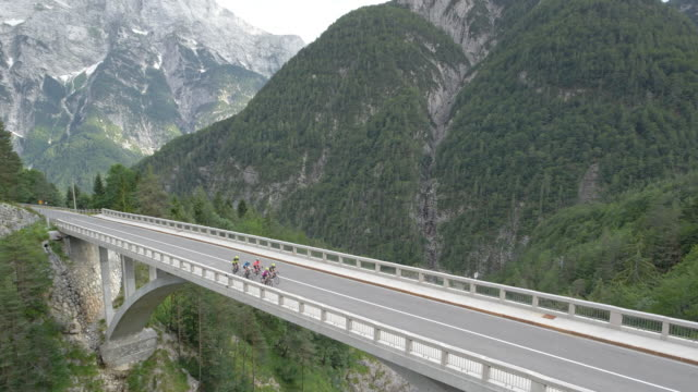 AERIAL Group of people riding road bicycles across a viaduct in the mountains