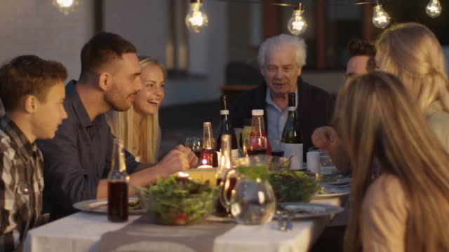 group of people sitting around a table, eating, communicating and having fun during family gathering dinner - family trees stock videos and b-roll footage