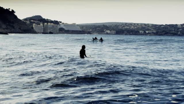 stockvideo's en b-roll-footage met groep mensen surfen in de zee. zon weerspiegelt in golven - baai