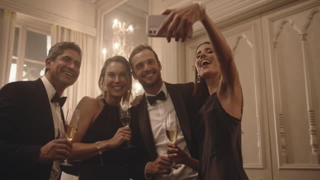 vídeos de stock e filmes b-roll de group of people taking a selfie at party - elegante
