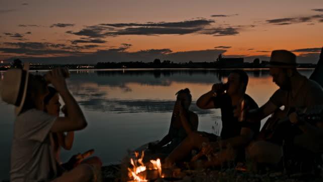 stockvideo's en b-roll-footage met slo mo groep mensen toasten met blikjes bier terwijl zittend bij een kampvuur - 25 29 jaar