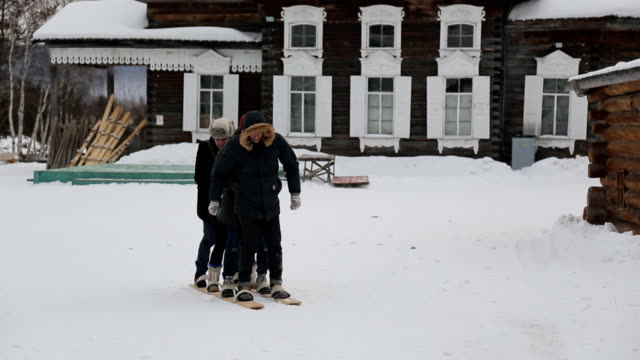 Group of people tries to move on one pair of wooden skiing video