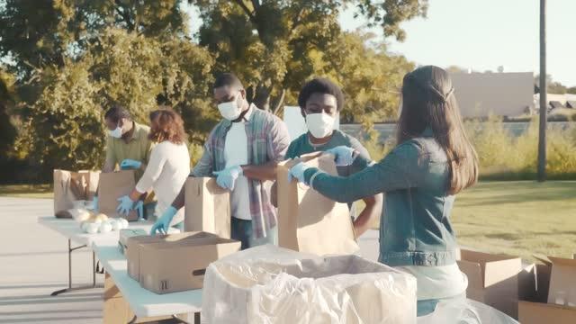 vídeos y material grabado en eventos de stock de grupo de personas como voluntario en food drive durante la pandemia de coronavirus - food drive
