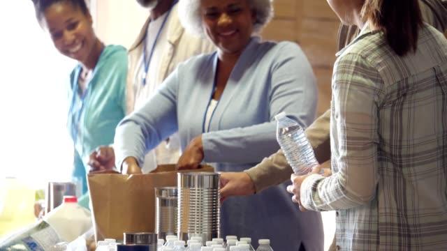 vídeos de stock, filmes e b-roll de grupo de pessoas de voluntariado no banco alimentar - voluntário
