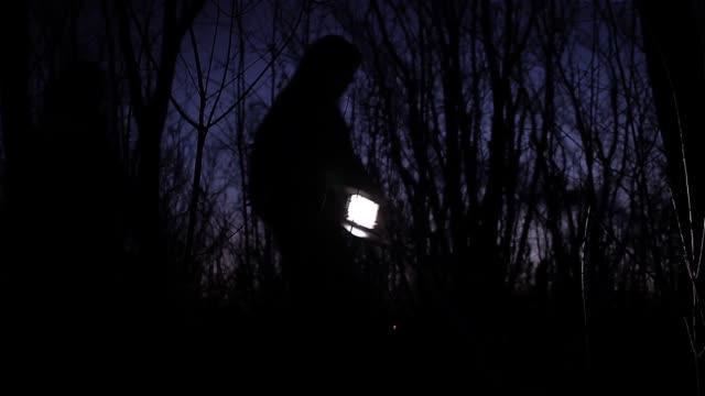 gruppo di persone che camminano per i boschi di notte. - cercare video stock e b–roll