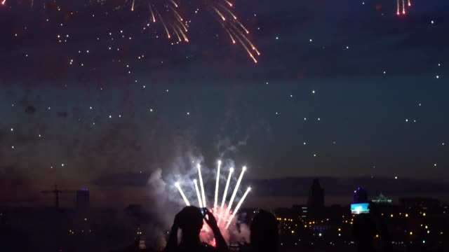 A group of people watching fireworks at night by the river. slow motion. HD