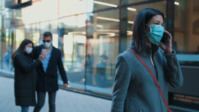 kirlilik maskesi takan bir grup insan yürüyen ve akıllı telefonlarda konuşan. - maske stok videoları ve detay görüntü çekimi