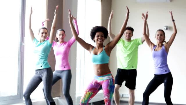 stockvideo's en b-roll-footage met groep mensen met coach dansen in de sportschool of studio - fitnessleraar
