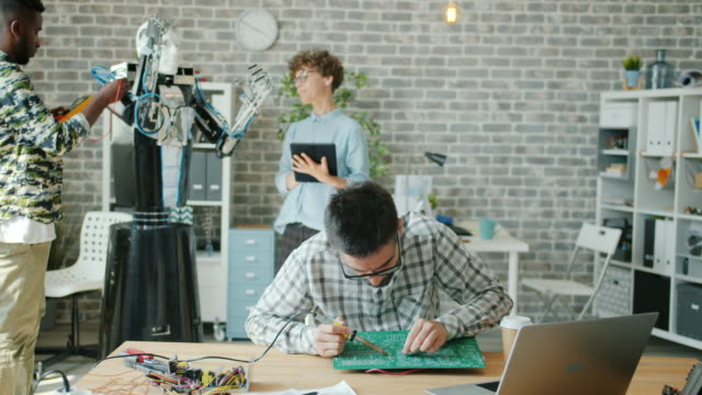 Group of people working in office testing robot and soldering motherboard