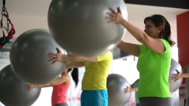 インストラクターに続いてジムでエクササイズボールで腕を鍛える人々のグループ - スポーツ用品点の映像素材/bロール