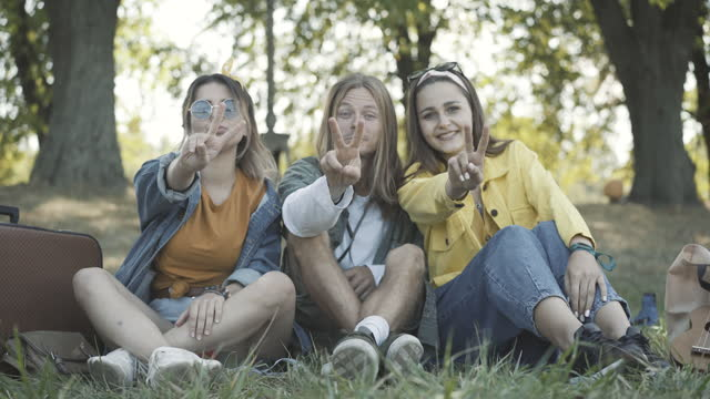 Group of positive hippies showing peace gesture and smiling. Happy relaxed Caucasian friends sitting on green summer grass outdoors. Carefree man and women posing on sunny day in 1960s.