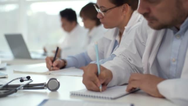 grupp av utövare skrift i anteckningsblock på medicinsk utbildning - seminarium bildbanksvideor och videomaterial från bakom kulisserna