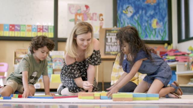 vídeos de stock, filmes e b-roll de grupo de estudantes do pre-school que trabalham com seu professor - professor de pré escola