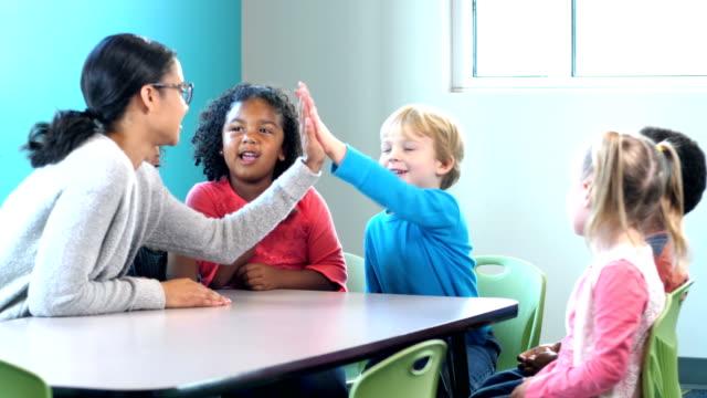 grupp av förskolebarn, pojkar blir high-five från lärare - förskoleelev bildbanksvideor och videomaterial från bakom kulisserna