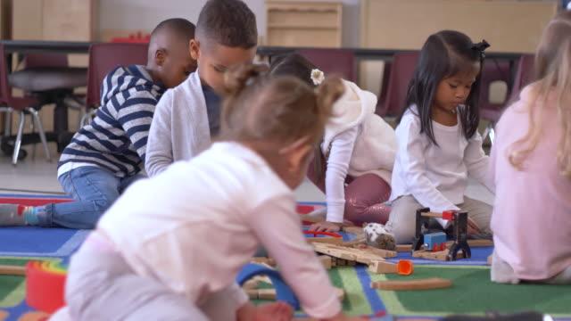vídeos y material grabado en eventos de stock de grupo de niños en edad preescolar jugando con juguetes - cuidado infantil