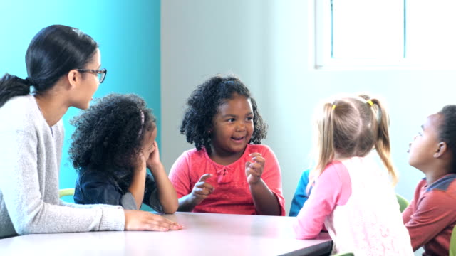 Group of preschoolers with teacher, girl talking A multi-ethnic group of preschool children sitting at a table with a teacher in a classroom. A little African-American girl is talking and her classmates are listening. The children are 4 years old. elementary age stock videos & royalty-free footage