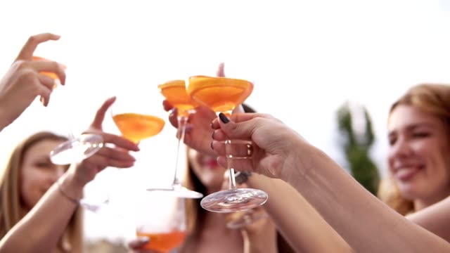 Group of pretty girls are celebrating and drinking cocktails from big glasses. Cheers. Outdoors. Aim frame of glasses, blurred background. Slow motion video