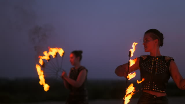 A group of professional circus performers with fire shows dance shows in slow motion using flame-throwers and rotating the torches burning objects.