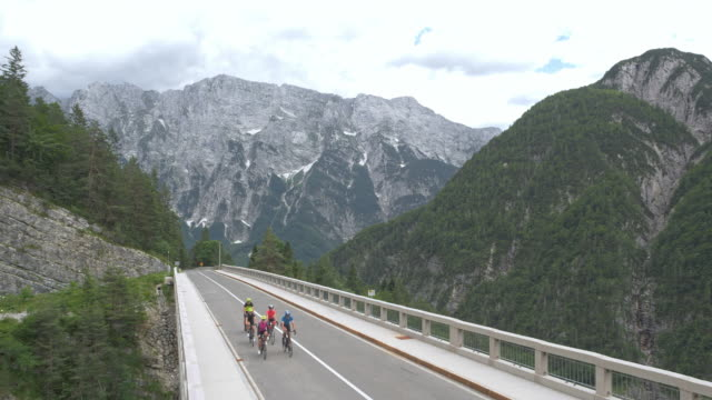 aerial a group of road cyclists riding across a viaduct - ciclismo su strada video stock e b–roll