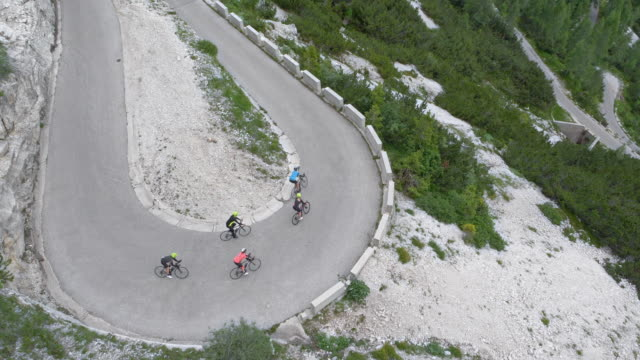aerial group of road cyclists riding down a mountain road overlooking the beautiful mountains and forests - ciclismo su strada video stock e b–roll