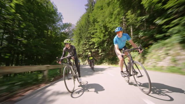 group of road cyclists speeding down a nice asphalt mountain road in sunshine - ciclismo su strada video stock e b–roll