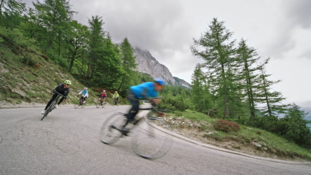 group of road cyclists speeding down the mountain road on a cloudy day - ciclismo su strada video stock e b–roll