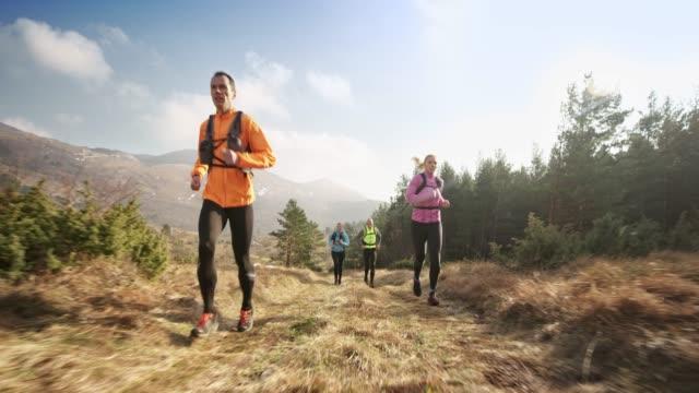 group of runners running on a grassy mountain trail in sunshine - 40 49 lat filmów i materiałów b-roll