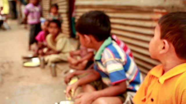 Group of rural children eating food asking for education
