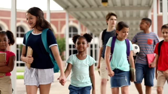 group of school children, friends walking together on campus. - età miste video stock e b–roll