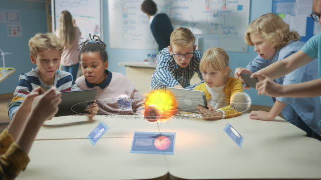 grupp av skolbarn i science class använd digital tablett datorer med augmented reality software, titta på pedagogiska 3d animation av solsystemet. vfx, specialeffekter render - digital device classroom bildbanksvideor och videomaterial från bakom kulisserna