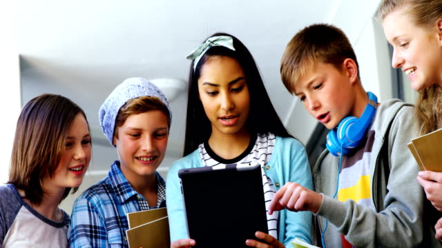grupp av skolkamrater som använder digitala tablett i korridor - digital reading child bildbanksvideor och videomaterial från bakom kulisserna