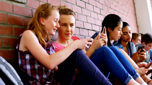 group of school friends using mobile phone 4k - preadolescente video stock e b–roll