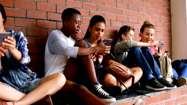 Group of school friends using mobile phone 4k video