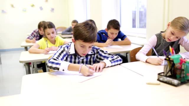 stockvideo's en b-roll-footage met groep van school-kids proef schrijven in de klas - schooljongen