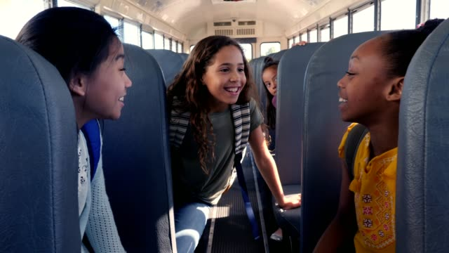 Group of schoolgirls load school bus after school Camera follows preteen school girl as she boards a school bus. She passes a cheerful female bus driver and then takes a seat. The girls begin to talk with one another. school buses stock videos & royalty-free footage