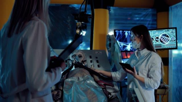 stockvideo's en b-roll-footage met groep wetenschappers het bestuderen van de vreemdeling vanuit de ruimte. artsen voeren een wetenschappelijk experiment op een vreemdeling in laboratoria. - ventilator bed