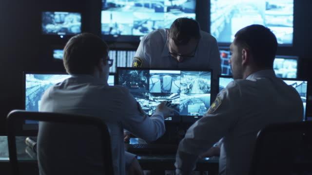 grupp av trygghet officierna har en konversation på arbetet i ett mörkt övervakning rum fyllda med skärmar. - vakta bildbanksvideor och videomaterial från bakom kulisserna