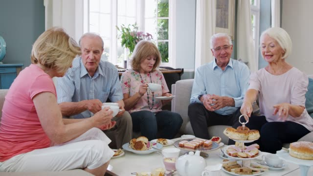 Group Of Senior Friends Enjoying Afternoon Tea At Home Together video