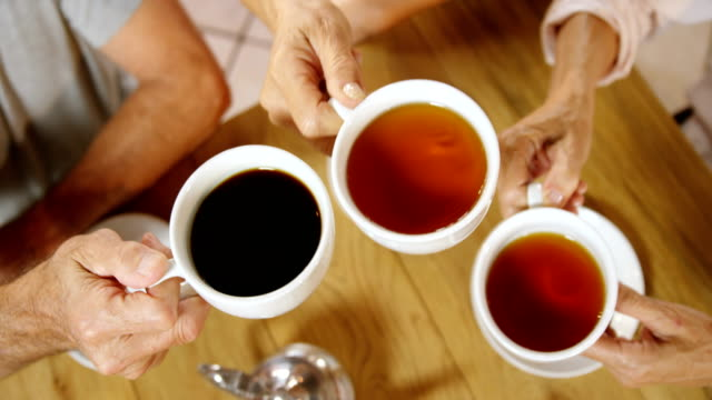 Group of senior friends toasting coffee cups 4k video