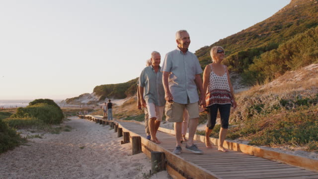 Group Of Senior Friends Walking Along Boardwalk At Beach On Summer Group VacationÊ Group of senior friends on vacation walking along wooden boardwalk coming back from beach - shot in slow motion retirement stock videos & royalty-free footage