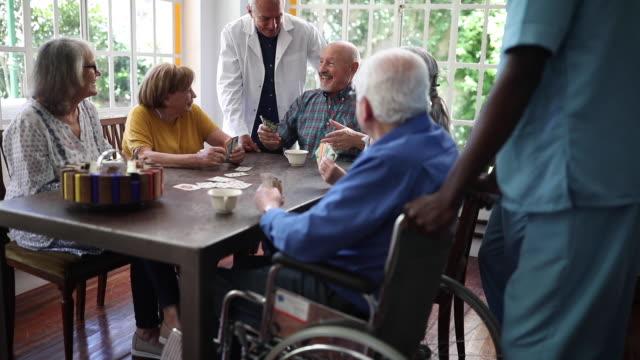 grupa starszych osób grających w karty w czasie herbaty - lifestyle filmów i materiałów b-roll