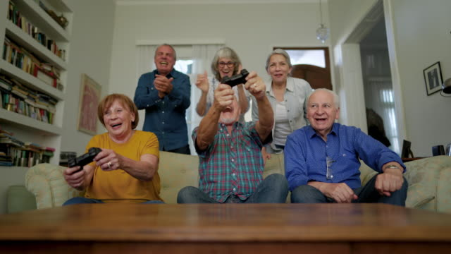 group of senior people playing video games and laughing - giovane nell'animo video stock e b–roll