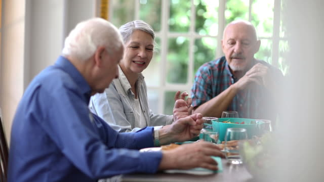 Group of seniors sharing food in retirement community video