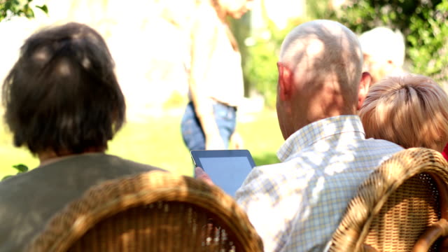 屋外デジタル タブレットを使用して高齢者のグループ - 老人ホーム点の映像素材/bロール
