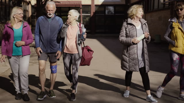 group of seniors walking away from community center - body positive video stock e b–roll