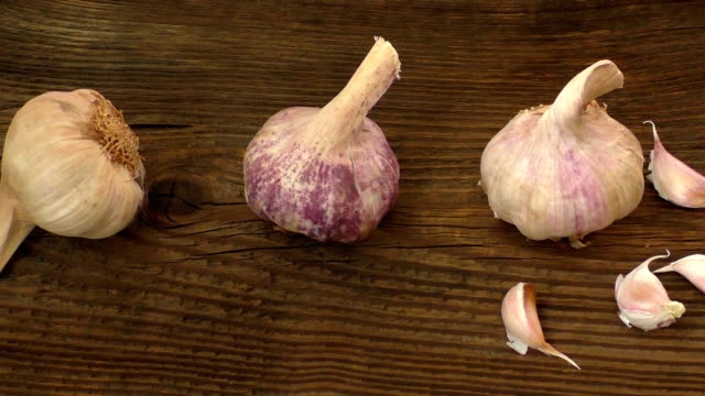 Group of single garlic cloves and a clump of garlic - video
