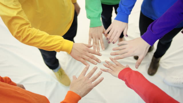 Group of six hands wearing gay pride long sleeve shirts in circle video