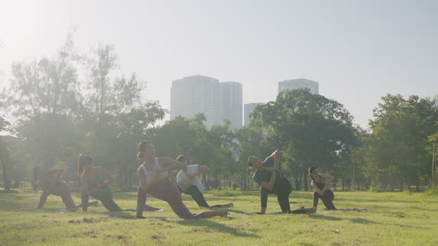 Group of six people mixed age people making yoga pose call noose pose in public park in city for fitness, sport, yoga and healthy lifestyle concept