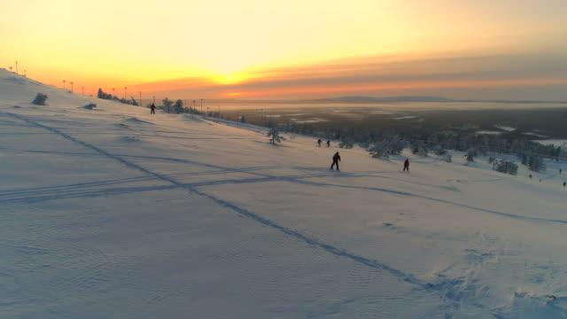 antenn: grupp av skidåkare skidåkning ner snöiga berg slutta på vintern sunset - finland bildbanksvideor och videomaterial från bakom kulisserna